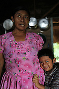 Cristina Peck, 47, Mopan Mayan cacao grower from San Jose, Toledo, stands in her kitchen with her five-year old son Arden. Cristina is married to Justino Peck who served as TCGA chairman from 1992 to 1997, once again from 2003 to 2010, and is currently the TCGA's liaison officer. Toledo Cacao Growers' Association (TCGA), San Jose, Toledo, Belize. January 25, 2013.