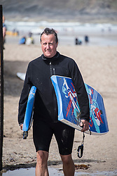 © Licensed to London News Pictures. 24/12/2014. Dean, Oxfordshire UK. Mr Cameron in Polzeath in August 2014. The Prime Minister was just yards away from a protest by Father for Justice having returned to his car after body boarding in the sea with his daughter. Fathers for Justice protestors plan to spend Christmas protesting in the village of Dean where the Prime Minister David Cameron lives. Photo credit : MARK HEMSWORTH/LNP