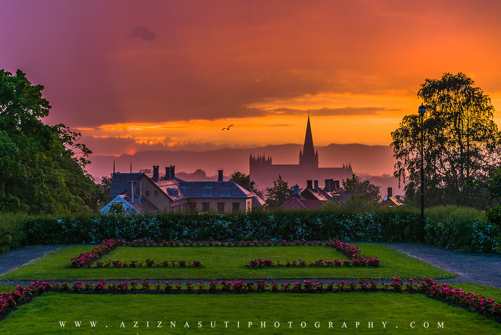 I shot this picture after a heavy rain in Trondheim. The sky and the clouds were changing rapidly. I took several shots in the rain actuially I was almost like a wet blanket but man it worth it to see such a beautiful scenary. You see a silhouette of the Nidaros cathedral in the picture. note that this is a midnight sunset of the summer time in Trondheim. Clock 11 p.m Please feel free to check my photos here or find me by: |Website| ,|Facebook page| , |Instagram| ,|Google+| ,|Twitter |.
