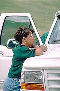African American woman age 20 deep in thought arms on truck.  Minneapolis Minnesota USA