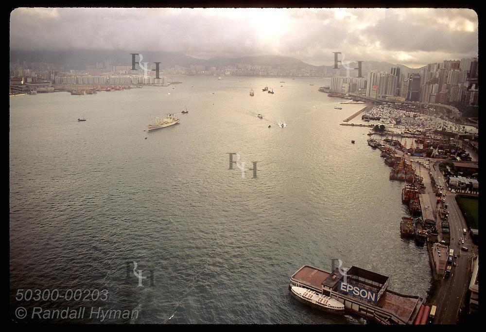 High-rises and skyscrapers ring harbor filled with boats in early morning aerial view toward east. Hong Kong