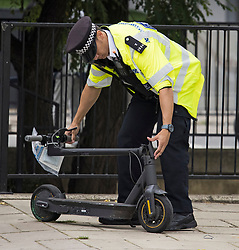 © Licensed to London News Pictures. 20/08/2021. London, UK. A police officer folding an e-scooter which was confiscated during a routine operation on the Harrow Road in Maida Vale, north west London. The use of privately owned e-scooters remains illegal except for on private land. A number of rental schemes are currently being trialed across the UK. Photo credit: Ben Cawthra/LNP