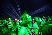 KOSTRZYN, POLAND - AUGUST 04: A woman lit with green stage lights is seen among other crowd members during a rock concert at the 2017 Woodstock Festival Poland on August 4, 2017 in Kostrzyn, Poland. The three-day rock music festival, now in its 23rd year, brings together hundreds of thousands of music fans from across Central Europe. Festival organizers charge the fans no admission. (Photo by Omer Messinger/Getty Images)