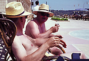 Two men bare chested sitting in sun drinking and smoking on holiday in the Mediterranean 1966