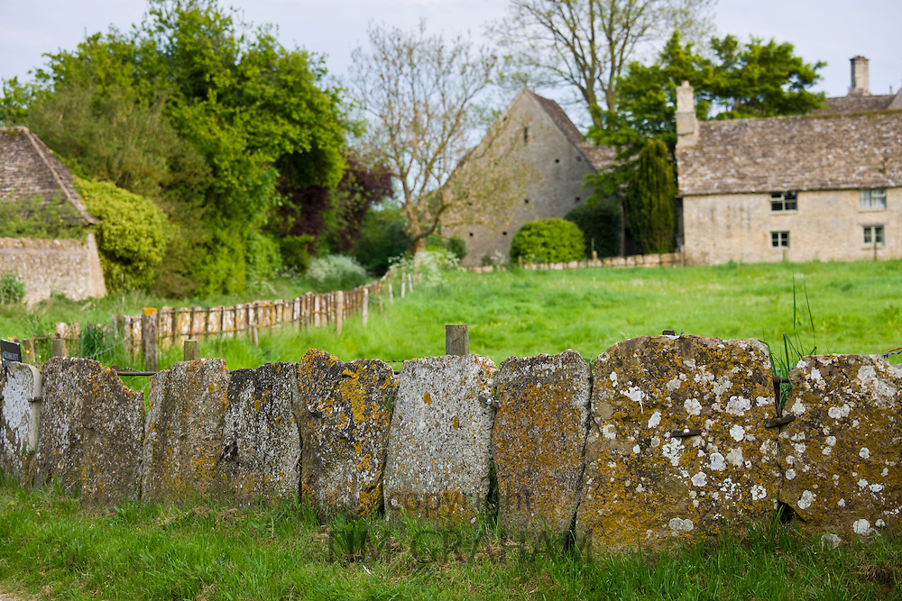 Cotswolds village, country lane and old stone slab fencing in Kelmscott, The Cotswolds, Gloucestershire, UK