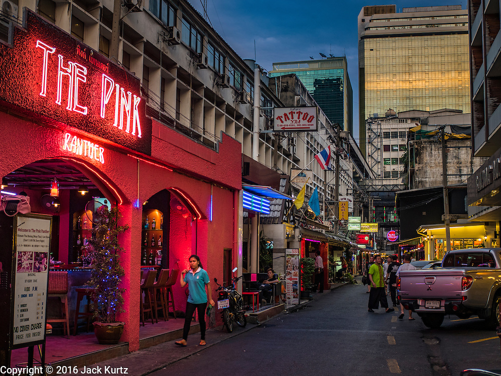 """26 MAY 2016 - BANGKOK, THAILAND: A woman walks past the """"Pink Panther,"""" one of the bars in the Patpong adult entertainment district in Bangkok.          PHOTO BY JACK KURTZ"""