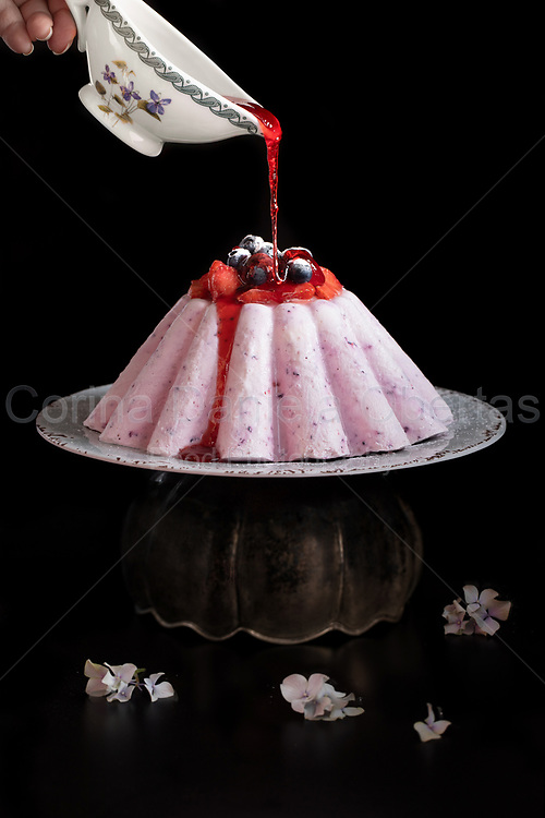 Hand with sauce boat pouring syrup over ice cream cake of yogurt and berries.