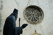 Statue of Bishop Augustin Kazotic, with rose window of church of Sveti Duje (Saint Dominic) Monastery in background. Trogir, Croatia