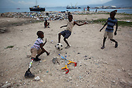 Sebastien, 10, plays goalie during a soccer game with friends and cousins along the waterfront in the tent camp where he lives in the Carrefour neighborhood of Port-au-Prince, Haiti.  His mother was killed and his leg crushed in the January 12 earthquake.