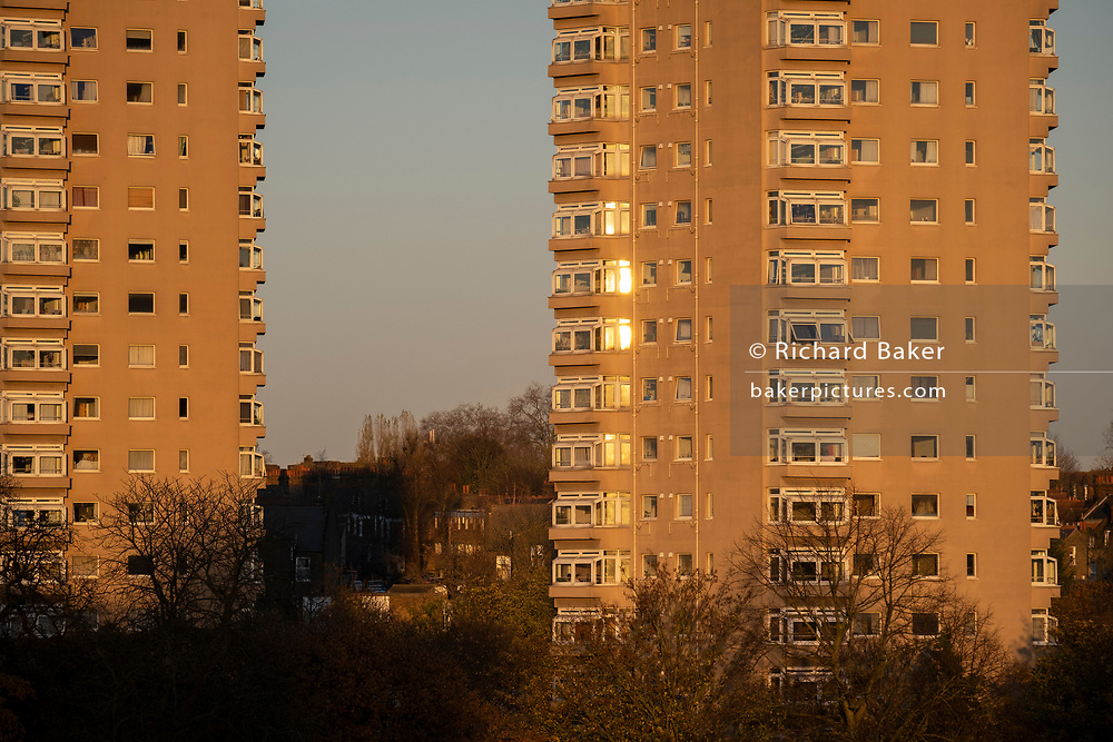 High-rise tower block windows have  the glow of a setting sun in Herne Hill in Lambeth, on 19th November 2020, in Lambeth, London, England.