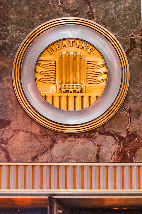 A machine-age, Art Deco, brass medallion, or roundel on the Empire State Building's marble-walled lobby -- one of 11 such roundels, each honoring a different technology or craft essential to the construction of the great building. This one celebrates heating technology.