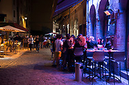 People sit at a cafe at night in Lyon, France.