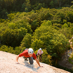 A couple rock climbing near the top of Cathedral Ledge.  Echo Lake State Park in North Conway, New Hampshire.  White Mountains.