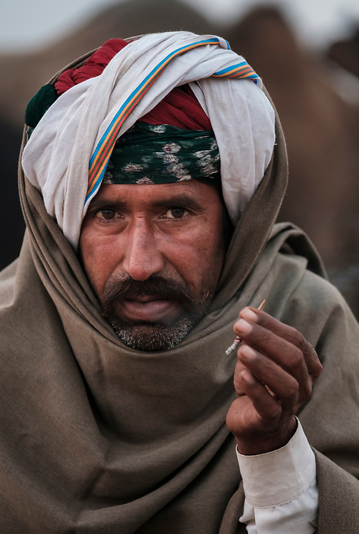 PUSHKAR, INDIA - CIRCA NOVEMBER 2016: Cameleer smoking early morning in the Pushkar Camel Fair grounds. It is one of the world's largest camel fairs. Apart from the buying and selling of livestock, it has become an important tourist attraction.