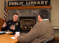 Gilford Police Chief Anthony Bean-Burpee is joined by John Larrere during Coffee with the Chief at Gilford Library on Monday morning.   (Karen Bobotas/for the Laconia Daily Sun)