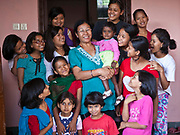 Nepalese female children stand around their care home staff, who they call 'Aunty' in K House, Kathmandu, Nepal.  The care home is run by Friends of Needy Children organization.  It rescues children and provides a loving home for boys and girls who are orphaned or abandoned.  Abject poverty, domestic violence and armed conflict have caused many Nepalese children orphaned and homeless.