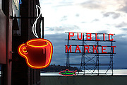 A red neon coffee sign and the red neon Public Market sign atop the Pike Place Market in Seattle, Washington.
