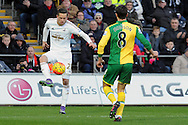 Swansea's Gylfi Sigurdsson controls the ball watched by Norwich's Jonny Howson. Barclays Premier league match, Swansea city v Norwich city at the Liberty Stadium in Swansea, South Wales on Saturday 5th March 2016.<br /> pic by  Carl Robertson, Andrew Orchard sports photography.