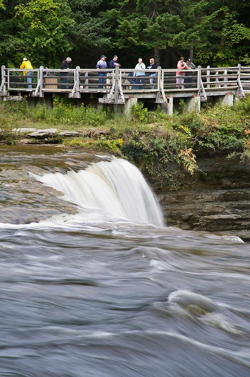 Tourists view the Upper Falls at Tahquamenon Falls State Park near Newberry Michigan.