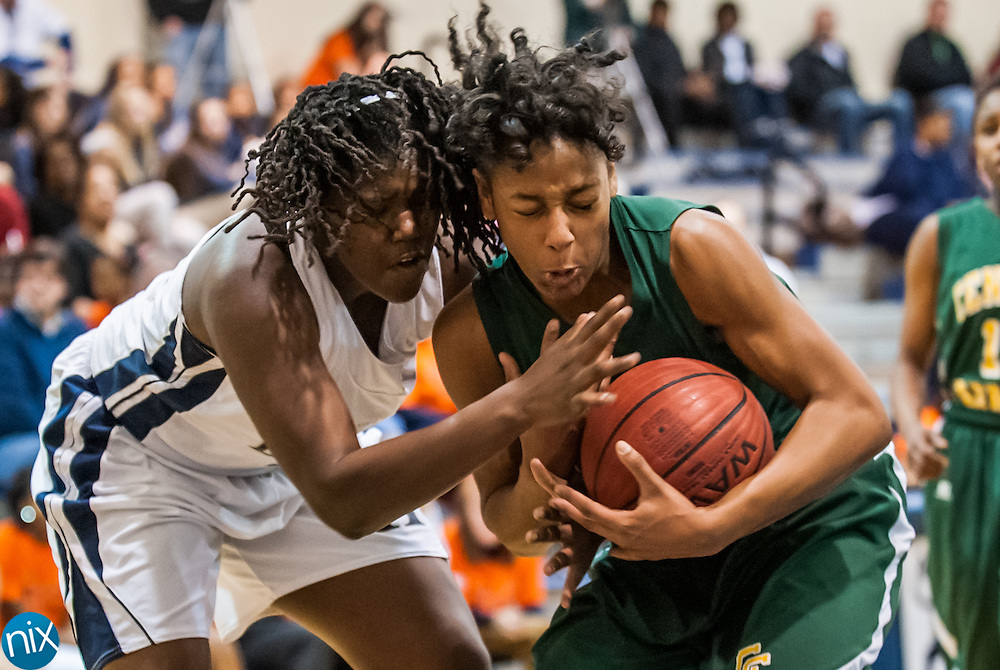 Hickory Ridge's Zharia Brown (22) and Central Cabarrus' Elanna Peay (23) fight for a rebound Friday night at Hickory Ridge High School in Harrisburg. The Ragin' Bulls won the game 58-52.