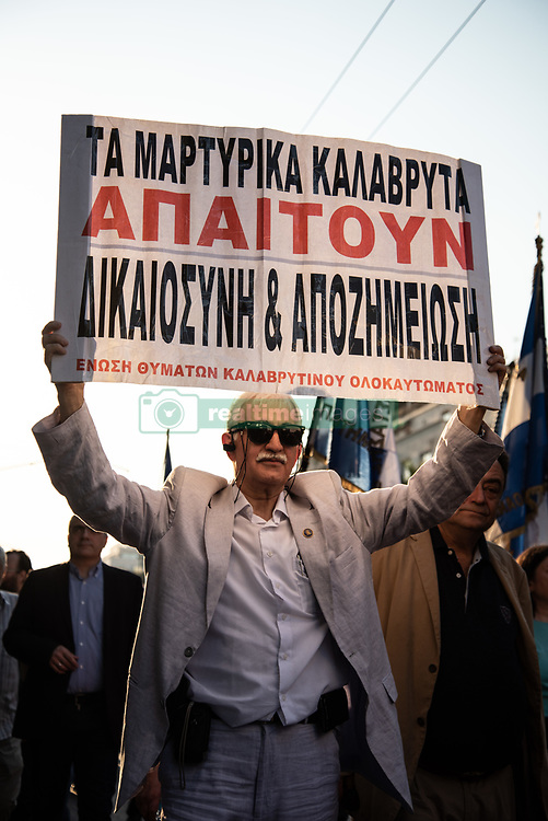 April 27, 2018 - Athens, Greece - A protester seen holding a placard during the demonstration..First gathering at the Unknown Soldier's Monument, the march has been made until the German Embassy to protest for compensation of the World War II from Germany as several massacre perpetuated by German soldiers back in 1943 were committed. (Credit Image: © Vangelis Evangeliou/SOPA Images via ZUMA Wire)