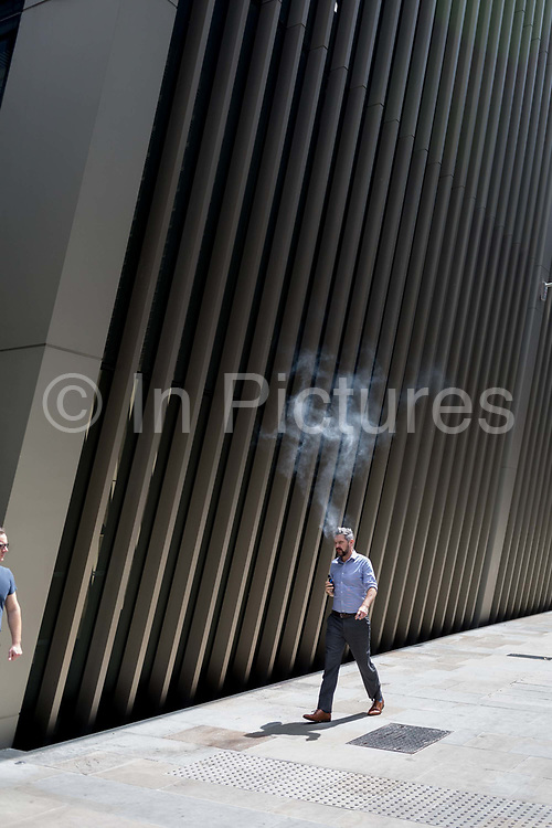 A man exhales vape smoke while walking along a street in the City of London, the capitals financial district aka the Square Mile, on 10th July 2019, in London England.