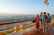 Mandalay, Myanmar - November 8, 2011: Three tourists visiting Mandalay Hill talk with a Buddhist monk.