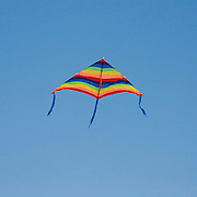 Colourful kite flying in a blue sky