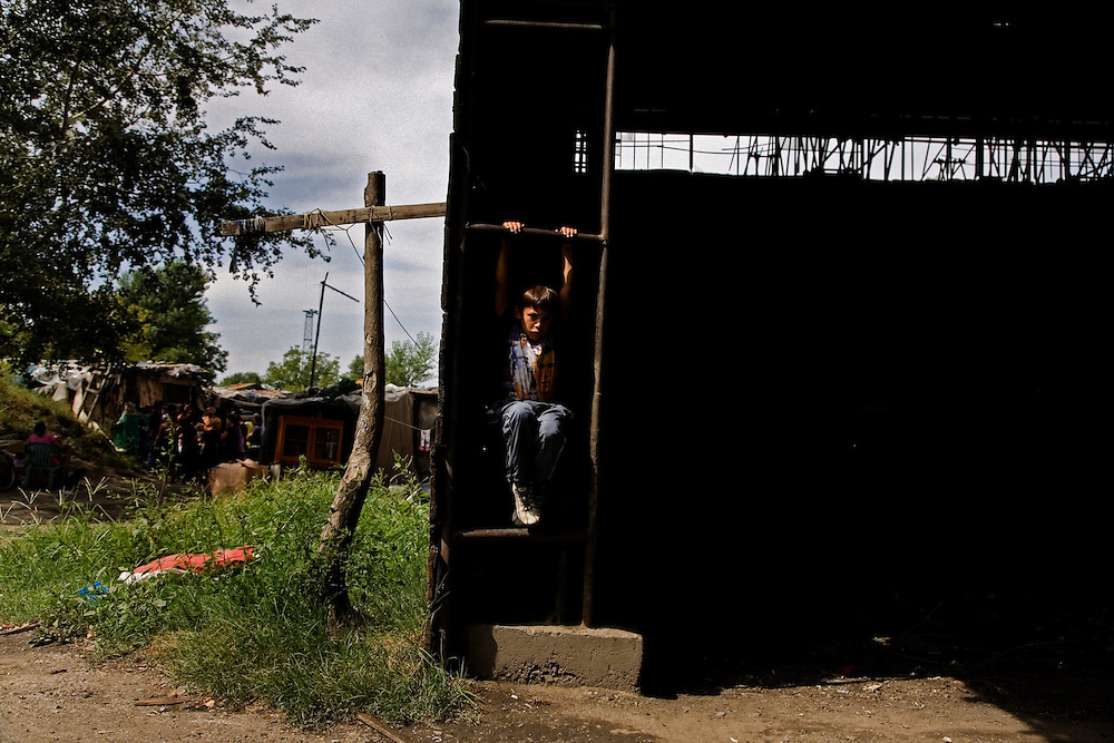 A boy from the Stara Gazela settlement plays while the camp waits for government officials to arrive and sweep the camp.