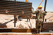 12 JUNE 2006 - SAN LUIS, AZ: Utah Army National Guard soldiers use  heavy equipment to lift a section of fence into place on the US/Mexico border. Fifty five members of the 116th Engineer Company, Combat Support Engineers, of the Utah Army National Guard are in San Luis, AZ, to build a fence and improve roads east of the San Luis Port of Entry on the US/Mexico border. The unit is the first of an estimated 6,000 US military personnel, almost all of them Army National Guard, who will be dispatched to the US/Mexico border by President Bush to help control immigration on the border. The Guardsmen will primarily build roads and fence and staff surveillance centers. They will not be engaged in first line law enforcement work.  Photo by Jack Kurtz
