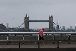 © Licensed to London News Pictures. 09/02/2020. London, UK. A jogger runs across London Bridge during windy weather this morning. Rain and windy weather is forecast today as Storm Ciara reaches the capital. Photo credit: Vickie Flores/LNP