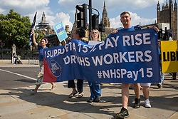 London, UK. 20th July, 2021. Matthew Tovey (r) and other NHS workers from the grassroots NHSPay15 campaign march from Parliament to 10 Downing Street to present a petition signed by over 800,000 people calling for a 15% pay rise for NHS workers. At the time of presentation of the petition, the government was believed to be preparing to offer NHS workers a 3% pay rise in 'recognition of the unique impact of the pandemic on the NHS'.