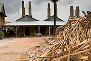30 JUNE 2006 - PHNOM PENH, CAMBODIA: Firewood from rubber trees stacked up in front of a brick factory in Phnom Penh, Cambodia. According the United Nations Food and Agricultural Organization, there are more than 70 brick factories in Phnom Penh and its environs. Environmentalists are concerned that the factories, most of which burn wood in their kilns, contribute to deforestation in Cambodia. They are encouraging factory owners to switch to burning rice husks, as brick kilns in neighboring Vietnam do. The brick factories are kept busy feeding Phnom Penh's nearly insatiable appetite for building materials as the city is in the midst of a building boom brought by on economic development and the need for new office complexes and tourist hotels.   Photo by Jack Kurtz / ZUMA Press