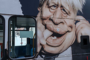 Four days before Christmas, a parody of Prime Minister Boris Johnson from Spitting Image is on the side of a London bus while retailers remain closed after the governments last-minute u-turn on the easing of Coronavirus pandemic rules. Instead, London and the South-East has been put under a Tier 4 restriction, forcing the closure of non-essential shops and small businesses, on 21st December 2020, in London, England.