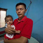"CAPTION: Cesar Lemus, 28 years old, seen with his daughter, Allison. She is his first child. Cesar works as an operator in a laboratory. He was thrilled when he learnt that his wife Lena was expecting a child. ""For me, being a father was special enough"", he says. ""The gender was not important to me, though my family wanted a girl"". He adds that having a child is something that money cannot buy. ""It is a gift from heaven! I had always dreamt of being a father, and would like to have two more children in the future"". LOCATION: In front of Stadium, Bario Abajo, Choloma, Cortes, Honduras. INDIVIDUAL(S) PHOTOGRAPHED: Allison Juliet Lemus Martinez (left) and Cesar Lemus Rodrigues (right)."