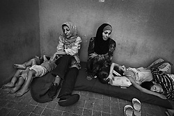 Zainab Suaidan and Fatima Kahwaji take shelter with their children from the bombing in a staircase at the Furn Al Shibak Secondary Public School for Girls in the Southern suburbs of Beirut, Lebanon, July 20, 2006. Zainab lost a leg years before in an Israeli attack against Lebanon and was fearful that her children would face the same fate. She left her home days before to escape the bombing, however her son remained in the home.