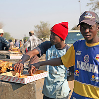 Africa, Namibia, Windhoek.  Men enjoying traditional Namibian street food snack of kapana - a mixture of sliced grilled red meat and fat - in the open-air market of Katutura.