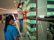 "27 MARCH 2015 - BANGKOK, THAILAND:  Workers clean display windows before the grand opening of ""EmQuartier"" a new mall in Bangkok. ""EmQuartier"" is across Sukhumvit Rd from Emporium. Both malls have the same corporate owner, The Mall Group, which reportedly spent 20Billion Thai Baht (about $600 million US) on the new mall and renovating the existing Emporium. EmQuartier and Emporium have about 450,000 square meters of retail, several hotels, numerous restaurants, movie theaters and the largest man made waterfall in Southeast Asia. EmQuartier celebrated its grand opening Friday, March 27.    PHOTO BY JACK KURTZ"
