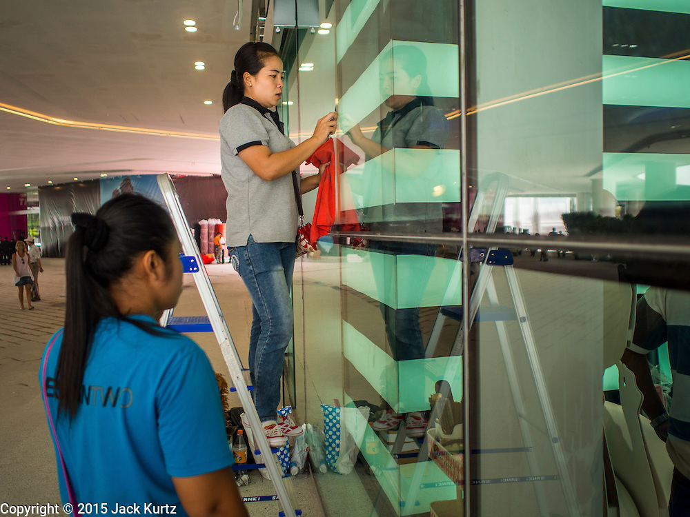 """27 MARCH 2015 - BANGKOK, THAILAND:  Workers clean display windows before the grand opening of """"EmQuartier"""" a new mall in Bangkok. """"EmQuartier"""" is across Sukhumvit Rd from Emporium. Both malls have the same corporate owner, The Mall Group, which reportedly spent 20Billion Thai Baht (about $600 million US) on the new mall and renovating the existing Emporium. EmQuartier and Emporium have about 450,000 square meters of retail, several hotels, numerous restaurants, movie theaters and the largest man made waterfall in Southeast Asia. EmQuartier celebrated its grand opening Friday, March 27.    PHOTO BY JACK KURTZ"""