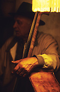 A Manouche man play double bass. Music is their life blood, an essential part of Roma, Gitan and Manouche culture. Often a singer will improvise on an old song, singing praises on homage to someone or of love or sorrow, of persecution ill treatment. Their history is often remembered, and shared in songs rather than written down.<br /><br />Europe, France, Camargue, Saintes Maries de la Mer. Gypsy music, dance and occasionally even bears are part of the traditional culture brought by Gypsies to the festival at Saintes Maries de la Mer, May every year. The Gypsy pilgrimmage brings gypsies from all over Europe for their annual festival.