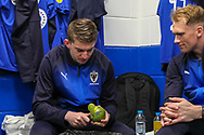 AFC Wimbledon defender Steve Seddon (15) peeling a mango during the EFL Sky Bet League 1 match between AFC Wimbledon and Gillingham at the Cherry Red Records Stadium, Kingston, England on 23 March 2019.