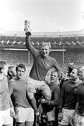 File photo dated 30/7/1966 of England's triumphant 1966 World Cup final captain Bobby Moore chaired by hat-trick hero Geoff Hurst (L) and Ray Wilson as he salutes the crowd with the Jules Rimet Trophy after the 4-2 victory against West Germany at Wembley. A London gangster and his brother were behind the notorious unsolved theft of the World Cup trophy just months before the 1966 tournament in England, it has been claimed.