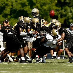 August 1, 2010; Metairie, LA, USA; New Orleans Saints defenders combine to tackle force a fumble by running back Chris Ivory (48) during a training camp practice at the New Orleans Saints practice facility. Mandatory Credit: Derick E. Hingle