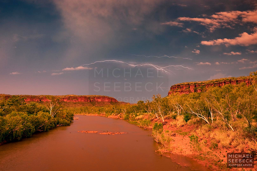 """A """"Crawler"""" lightning bolt appears in the sunset sky over the Victoria River after an intense lightning storm passed over."""
