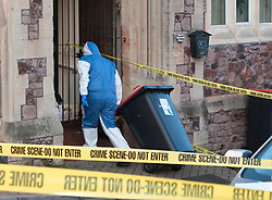 © Licensed to London News Pictures. 03/12/2014. Bristol, UK.  A forensics officer pulls a rubbish bin inside the old Hospital for Sick Children building in Royal Fort Road as Police and forensics search for Charlotte Bevan age 30 and her 4 day old baby daughter who went missing from the Bristol Maternity Hospital on St Michaels Hill opposite the search area. Photo credit : Simon Chapman/LNP