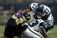 Seattle defenders Jordan Babineaux (27) and Marcus Trufant (23) tackle St. Louis Rams running back Tony Fisher (30) in the first half at the Edward Jones Dome in St. Louis, Missouri, October 15, 2006.  The Seahawks beat the Rams 30-27.<br />