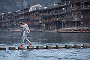 Boyfriend carrying girlfriend on piggyback while crossing a river on stepping stones, Fenghuang, Hunan Province, China