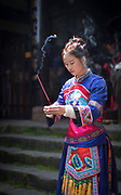 Three quarter length shot of an actress holding incense while preforming in a traditional Miao dress, Fenghuang, Hunan Province, China