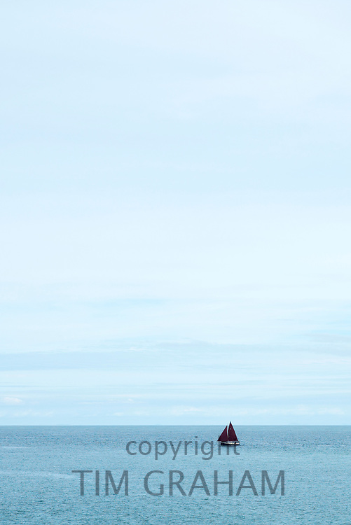 Single yacht pleasure boat with red sail sailing on still waters of calm ocean in the morning at Aberaeron, Pembrokeshire, Wales, UK