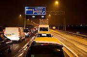 Filevorming na sneeuwbui op de snelweg A7 tijdens de avondspits bij de afslag naar de A8.File on a highway near Amsterdam caused by snow in the winter